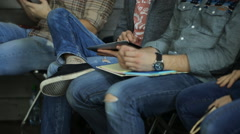 Young people sitting in a row, keep on their laps notebooks, smartphones and Stock Footage