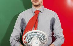 Midsection of businessman with sweaty armpits holding fan against colored - stock photo