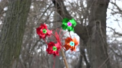 Children's toy pinwheel in the wind against a background of trees Stock Footage