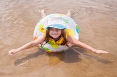 Little girl in the shallows lying on his stomach in the inflatable ring outst Stock Photos