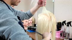 Future barber learns to make women's hairstyle on a mannequin artificial hair - stock footage