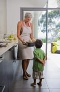 Woman showing baking dish to boy - stock photo