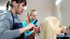 Girls learn the profession of female hairdresser trained on artificial hair. Stock Footage