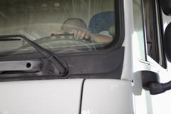 Low angle view of driver sleeping in truck seen through windshield Kuvituskuvat