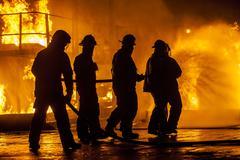 Firefighters hosing down fire Kuvituskuvat