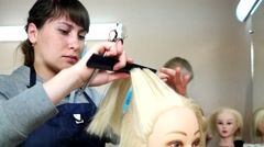 Students practiced in hairstyle female hair on the heads of the dummies blond. - stock footage