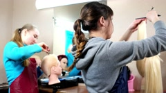 To do no harm to the living girls learn to cut hair on mannequins. - stock footage