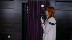 Woman photographer with red hair makes a photo on the camera Stock Footage