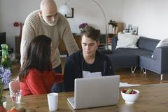 Parents talking with son by table with laptop at home Stock Photos