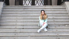 Street fashion. Cute models sitting on the stairs on a city street. Stock Footage
