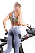 Fitness woman running on treadmill in gym - stock photo