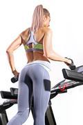 Fitness woman running on treadmill in gym Kuvituskuvat