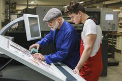 Young worker looking at mature colleague doing quality check of printout with - stock photo