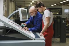 Mature worker showing colleague quality of printout with scanner at printing Stock Photos