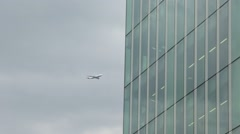 Jet Airliner Flies Past Glass Skyscraper Stock Footage