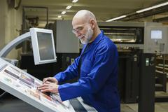 Mature man doing quality check of printout with scanner at printing press Stock Photos