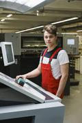 Portrait of young worker holding scanner over printout with machinery at - stock photo
