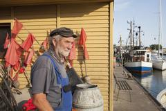 Senior man standing at harbor by boats moored at lake Stock Photos
