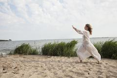 Side view of woman practicing yoga on sea shore against sky Stock Photos