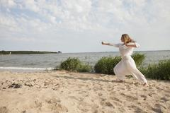 Young woman practicing yoga on sea shore at beach against sky Stock Photos
