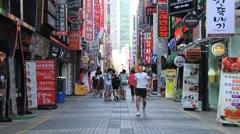 People walk by the street in downtown Busan, Korea. Stock Footage