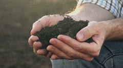 Farmer's hands holding pile of soil on fertile agricultural land Stock Footage