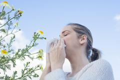 Woman sneezing in a daisy flowers meadow Stock Photos