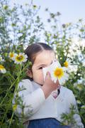 Toddler girl sneezing in a daisy flowers - stock photo