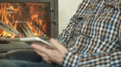 Male by the fireplace in  room, use tablet - stock footage