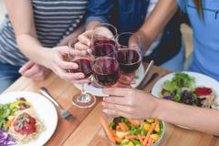 Friends toasting glass of red wine while having meal Stock Photos