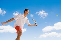 Man leaping to play smash shot at tennis - stock photo