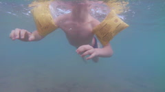 Following a young swimmer shot from underwater as he paddles along the surfac Stock Footage