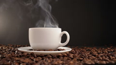 cup with hot drink on roasted coffee beans. dolly shot - stock footage
