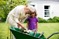 Granny with grandson looking at flowers in wheelbarrow Stock Photos