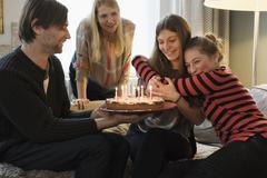 Happy family celebrating a birthday at home Stock Photos