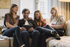 Happy family with father using digital tablet in living room Stock Photos