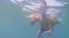 Underwater shot of young boy swimming with arm bands in the ocean Stock Footage