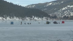 Ice fishing on mountain Lake, interior BC, wide establishing shot Stock Footage