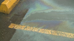 Environment, vehicle gasoline spill in parking lot Stock Footage