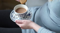 4k hands with pretty vintage cup and saucer having tea and heart biscuits Stock Footage