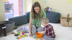 Mother with cute toddler daughter. Girl put wooden bricks in plastic bowl. Stock Footage