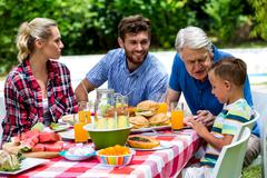 Granfather assiting grandson while having lunch Stock Photos