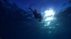 Ocean scenery tracks female swimmer, people or person in shot, on water surface, Stock Footage