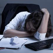 Frustrated office worker lying on the desk Stock Photos