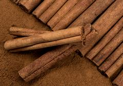 Cinnamon Sticks laying atop Ground Cinnamon with Three Sticks Askew - stock photo