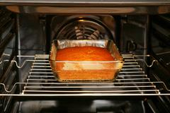 Cake in rectangular glass form is baked in the oven - stock photo