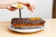 Chef decorate baked cake with chocolate and orange chips - stock photo