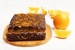 Chocolate and orange cake with a piece cut off near orange on white wooden ba - stock photo