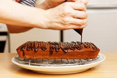 Chef decorate baked cake with chocolate - stock photo