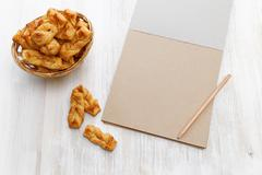 Plait cookies. Puff pastry with cinnamon near notebook for recipes and pencil Stock Photos